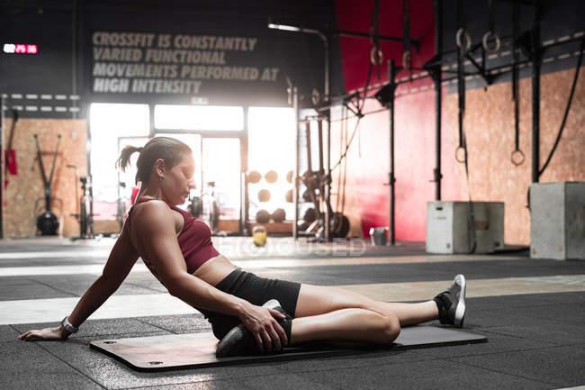 Вид сбоку молодого гибкого спортсмена, делающего упражнения на растяжку ног на коврике во время тренировки в спортклубе — стоковое фото