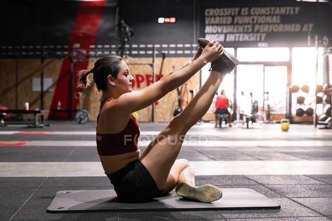 Side view of young flexible focused athlete doing stretching exercises for legs on mat during workout in sport club — Stock Photo