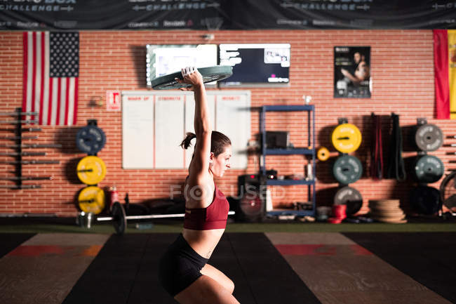 Вид сбоку сильного молодого спортсмена, делающего приседания с железной штангой во время тренировки в спортзале — стоковое фото