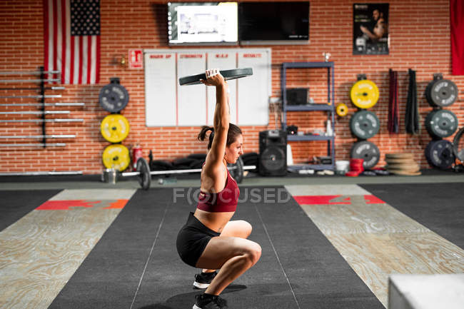 Side view of strong young enduring athlete doing squats with iron barbell disk during exercise in gym — Photo de stock