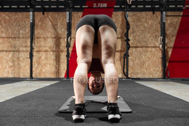 Сосредоточенный спортсмен делает упражнения на растяжку на коврике во время тренировки в спортклубе — стоковое фото