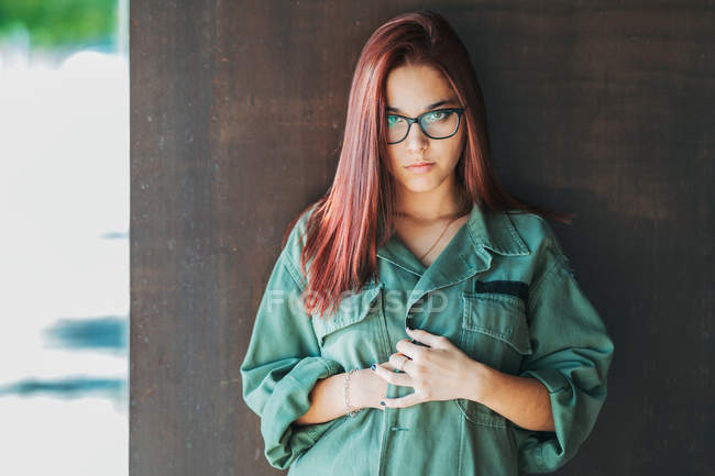 Contenuto elegante adolescente in occhiali in camicia verde scuro vicino parete marrone guardando la fotocamera — Foto stock