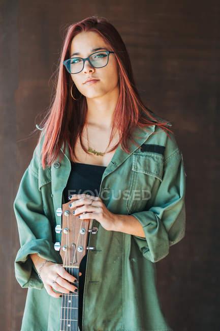 Контентний стильний підліток у окулярах темно-зеленої сорочки, що тримає гітару поблизу коричневої стіни, дивлячись на камеру. — стокове фото