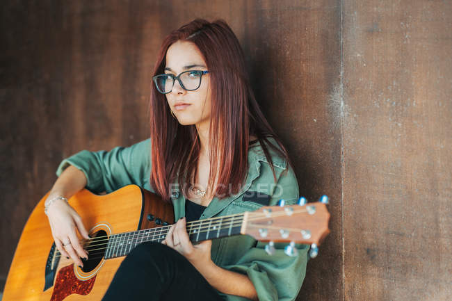 Seitenansicht des stilvollen Inhalts Teenager, der nachdenklich Gitarre spielt, mit überkreuzten Beinen auf dem Boden sitzt und in die Kamera blickt — Stockfoto