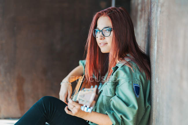 Side view of stylish content teenager thoughtfully playing guitar sitting on ground with crossed legs and looking at camera — Stock Photo