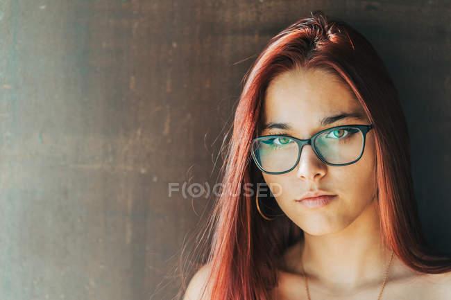 Contenu adolescent élégant dans des lunettes à proximité mur brun regardant la caméra — Photo de stock
