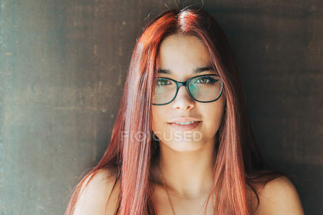 Контент стильний підліток у окулярах поруч коричневої стіни дивлячись на камеру — стокове фото