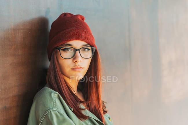 Adolescent élégant réfléchi dans un chapeau chaud et des lunettes en chemise vert foncé à proximité mur brun regardant le long — Photo de stock