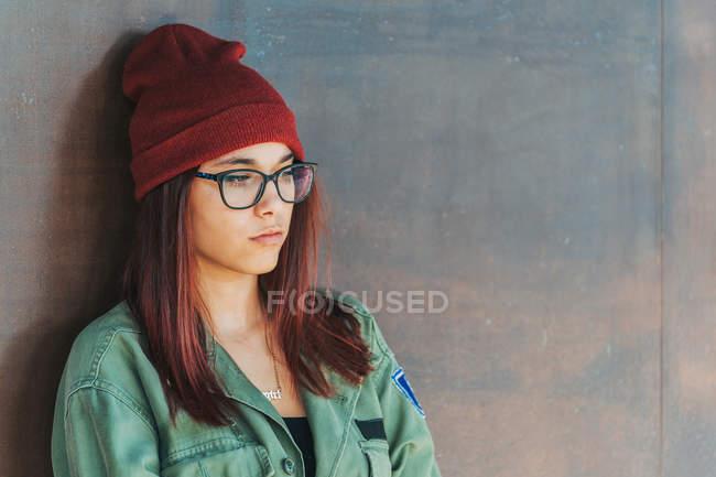 Nachdenklich stilvoller Teenager mit warmem Hut und Brille in dunkelgrünem Hemd neben brauner Wand, der mitschaut — Stockfoto