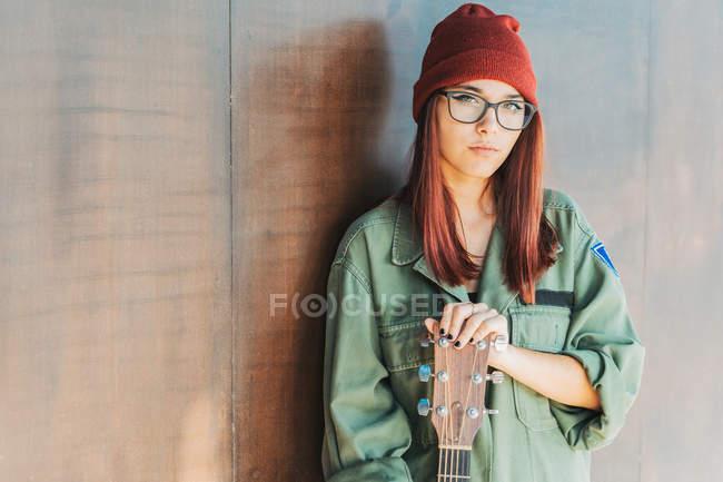 Содержание стильный подросток в очках в темно-зеленой рубашке держа гитару, стоящую рядом коричневая стена, глядя на камеру — стоковое фото