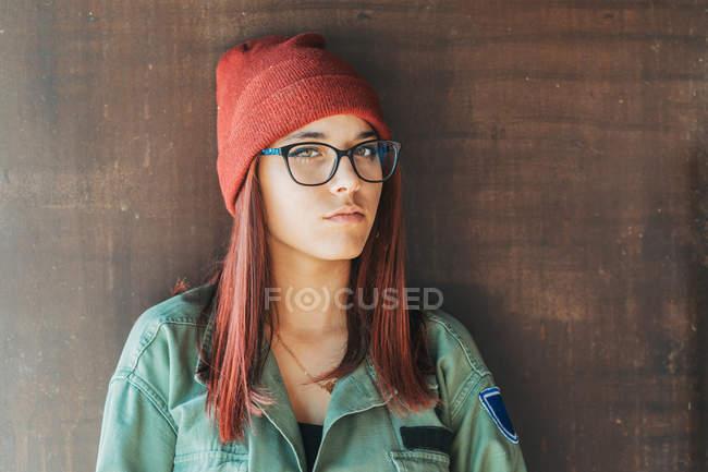 Pensante adolescente elegante em chapéu quente e óculos em camisa verde escuro nas proximidades parede marrom olhando ao longo — Fotografia de Stock