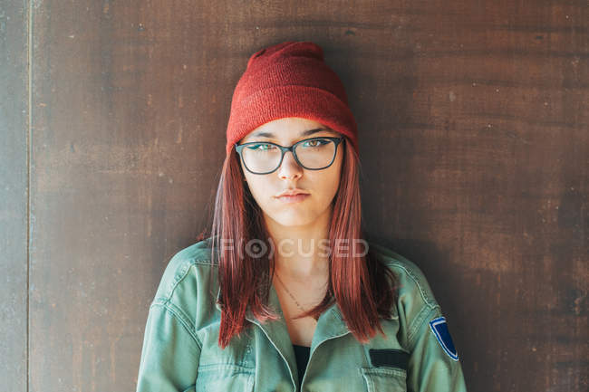 Thoughtful stylish teenager in warm hat and glasses in dark green shirt nearby brown wall looking along — Stock Photo