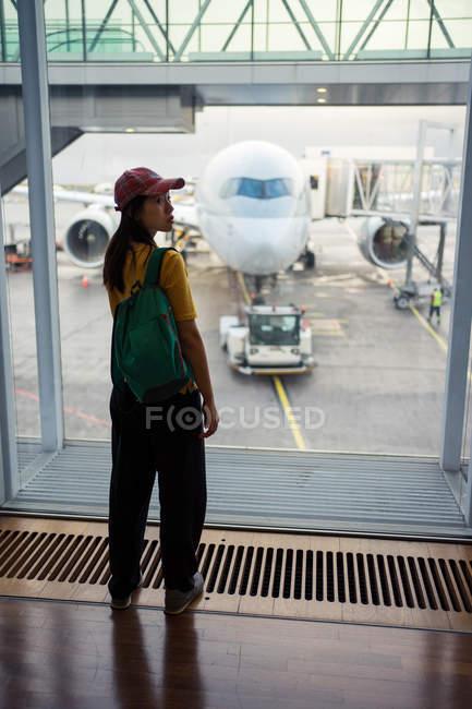 Visão traseira da mulher em boné, mochila e desgaste esportivo esperando no aeroporto — Fotografia de Stock