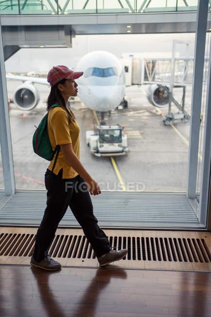 Vista lateral da mulher em boné, mochila e desgaste esportivo andando no aeroporto — Fotografia de Stock