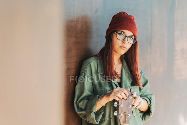 Content stylish teenager in glasses in dark green shirt holding a guitar standing nearby brown wall looking at camera — Stock Photo