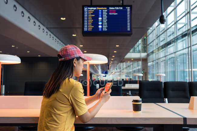Vue latérale de la femme asiatique en casquette surf téléphone mobile et boire du café de casquette jetable à table à l'aéroport — Photo de stock