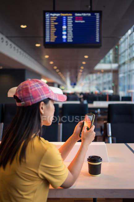 Rückansicht einer Frau mit Schirmmütze, die am Tisch im Flughafen Handy surft und Kaffee aus einer Einwegkappe trinkt — Stockfoto