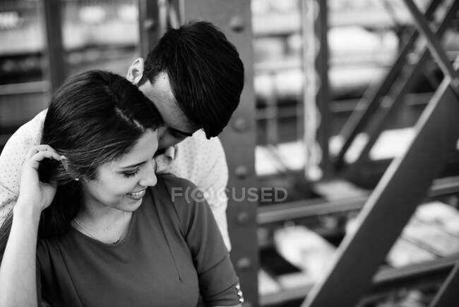 Liebender Mann und zarte Frau in blauem Kleid umarmen sich auf Eisenbahn unter Metallbrücke — Stockfoto