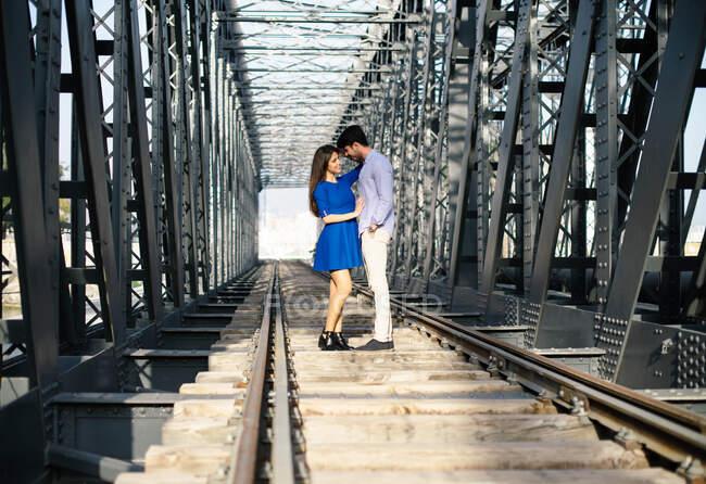 Uomo amorevole e tenera donna in abito blu che abbraccia sulla ferrovia sotto la costruzione di ponti in metallo — Foto stock