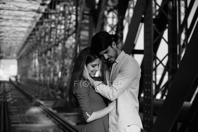 Hombre cariñoso y mujer tierna en vestido azul abrazándose en el ferrocarril bajo construcción de puente de metal - foto de stock