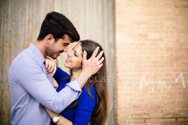 Side view of loving man and woman in elegant clothes kissing on background with columns — Stock Photo
