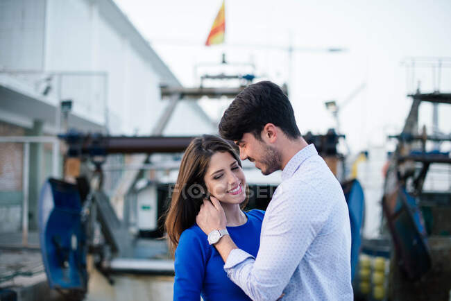 Vue latérale de charmante femme en robe bleue dans étreinte avec bel homme collant sur la jetée du port de la ville avec le navire sur fond — Photo de stock
