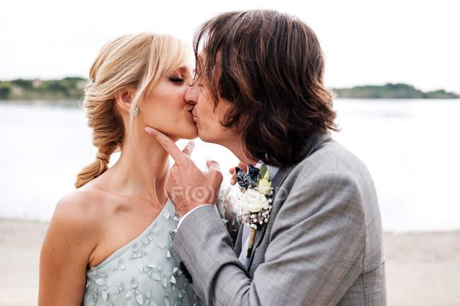 Радостный молодой жених в свадебном костюме обнимает и целует блондинку с волосами невесты в стильном платье позади на пустом песчаном побережье — стоковое фото