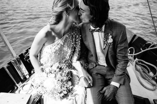 Задоволені подружні коханці в весільному одязі цілуються, відпочиваючи на човні з морем на задньому плані. — стокове фото