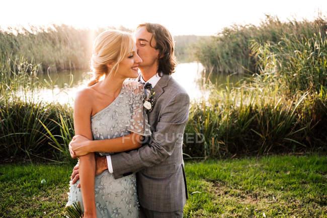 Stylisches frisch verheiratetes Paar in Hochzeitsanzügen umarmt und küsst sich mit grünen Pflanzen und nur an einem sonnigen Tag — Stockfoto