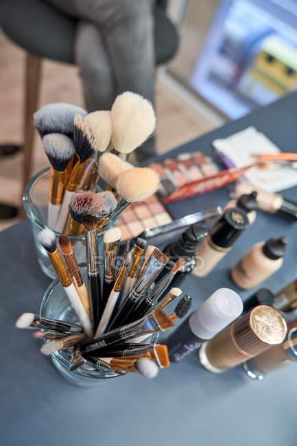 Dall'alto di spazzole di trucco diverse in occhiali e ombra di occhi con fondazione su tavolo in salone — Foto stock