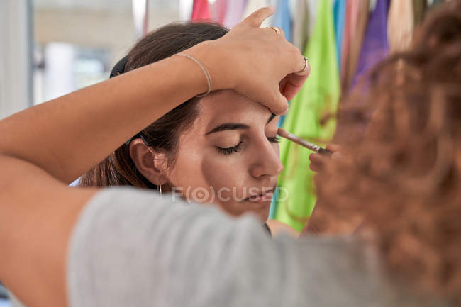 Concentrated makeup artist doing makeup on a beautiful woman client in a salon — Stock Photo