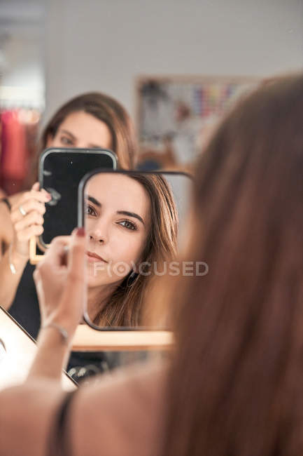 Reflection of a beautiful woman face in mirror in hand of smiling woman after cosmetic procedure in salon — Stock Photo