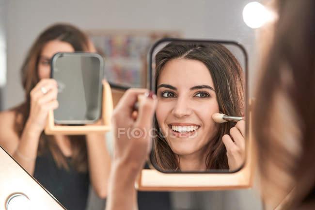 Donna dai capelli lunghi che compone sul viso disegno arrossire sulle guance con pennello guardando specchio in mano in salone di luce elegante — Foto stock