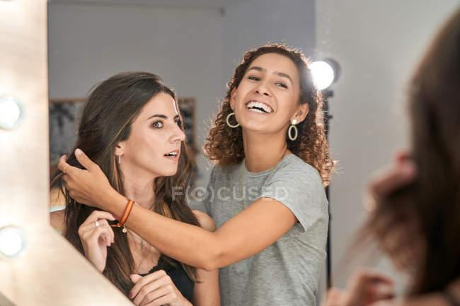 Réflexion dans le miroir du styliste et charmant longue chevelure belle femme dans un salon léger et élégant — Photo de stock