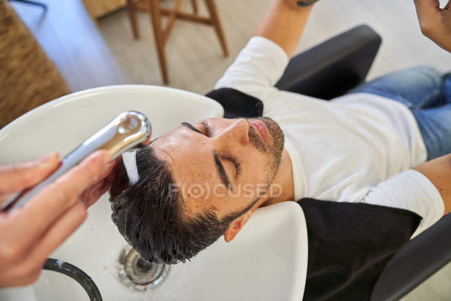 Barber washing the head with shampoo to a client with the head resting on the sink — Stock Photo