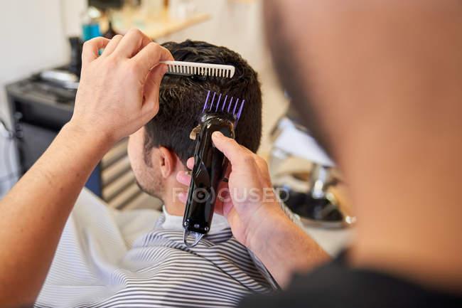 Перукарські стрижки з машиною для клієнта, який сидить на перукарському стільці — стокове фото