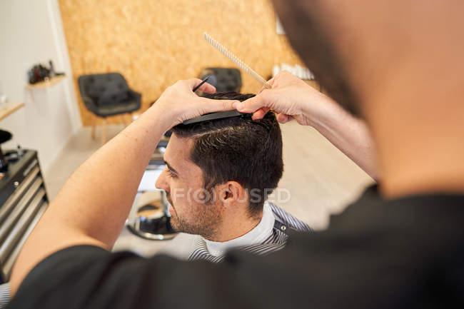 Парикмахер стрижет клиенту волосы, сидя на диване парикмахерской — стоковое фото