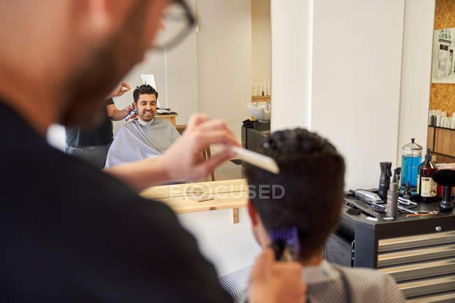 Парикмахер стрижет волосы машиной клиенту, сидящему на парикмахерском стуле. — стоковое фото