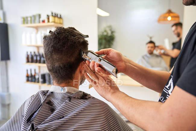 Клиент парикмахерской сидит в кресле и стрижет волосы. Парикмахерская и стиль жизни — стоковое фото