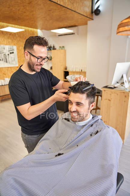 Парикмахер стрижет клиенту волосы бритвой. Парикмахерская и стиль жизни — стоковое фото