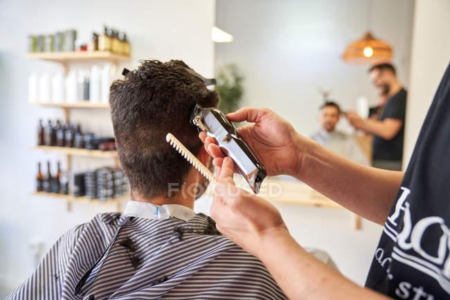 Costumiere in un barbiere seduto su una sedia e tagliando i capelli — Foto stock