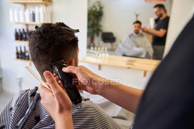 Barbiere taglio capelli da dietro le orecchie del cliente con un rasoio. Barbershop e stile di vita — Foto stock