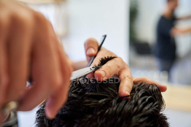 Barber cutting client hair with scissors — Stock Photo