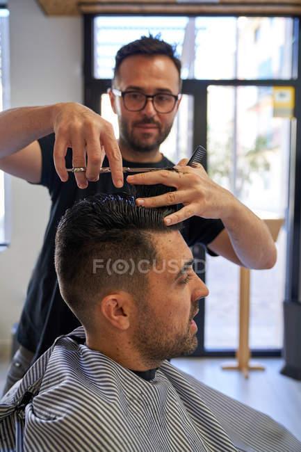 Парикмахер стрижет волосы ножницами и расческой клиенту. Дизайн и стиль — стоковое фото