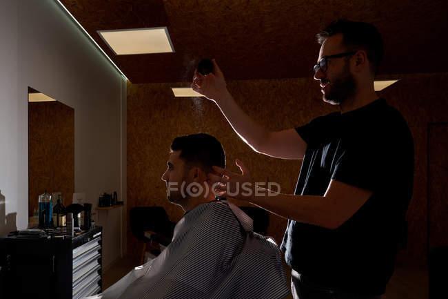 Coiffeur peignant et distribuant des produits de beauté à un client. Vintage et salon de coiffure — Photo de stock