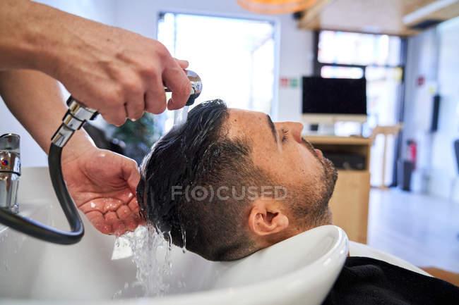Парикмахер моет голову шампунем клиенту с головой на раковине — стоковое фото