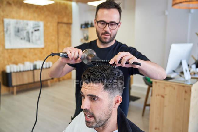 Парикмахер сушит волосы расческой и феном в парикмахерской. Парикмахерская и стиль жизни — стоковое фото