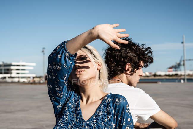 Attraktive nachdenkliche Frau, die sich mit der Hand vor dem Sonnenlicht bedeckt, während sie Rücken an Rücken mit einem jungen Mann sitzt — Stockfoto