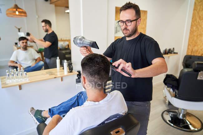 Парикмахер сушит волосы расческой и феном перед зеркалом — стоковое фото
