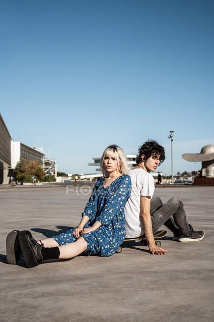 Attraktive sinnliche blonde Frau blickt in die Kamera, die mit Freund auf Skateboard vor blauem Himmel und Gebäuden auf dem Platz sitzt — Stockfoto